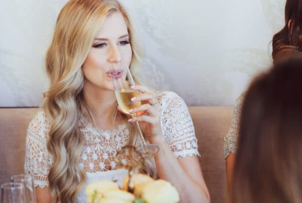 blonde lady sipping on champagne with high tea