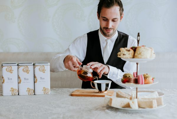 gentleman pouring tea with high tea
