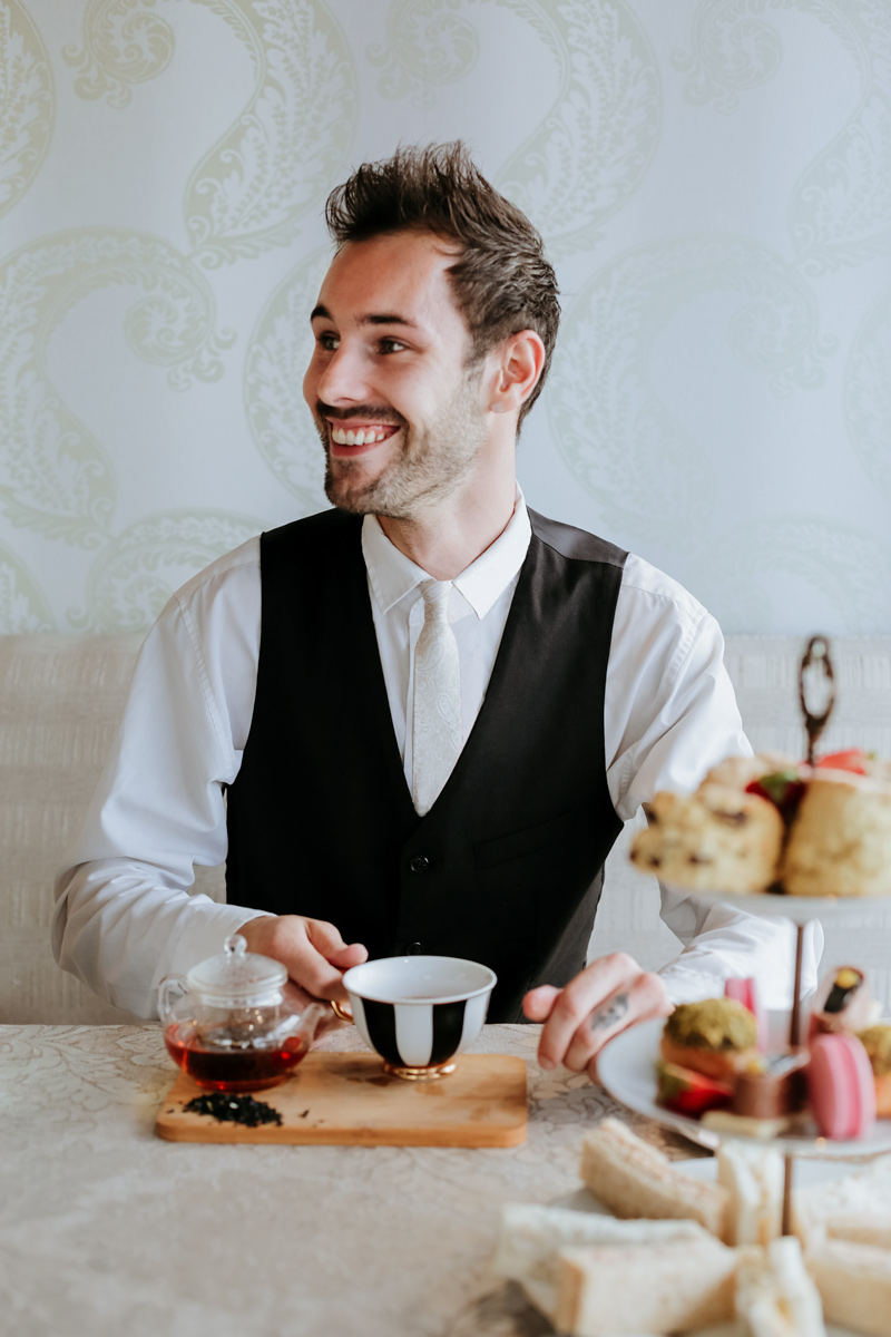 gentleman sitting with a cup of tea and a high tea